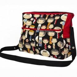 Bolso rojo con muñecas japonesas sobre fondo negro